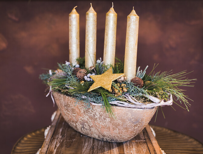 Adventskranz in einer ovalen goldenen Schüssel, gesteckt mit Nadelzweigen, Zapfen , einem goldenen Stern und 4 goldenen Stabkerzen.