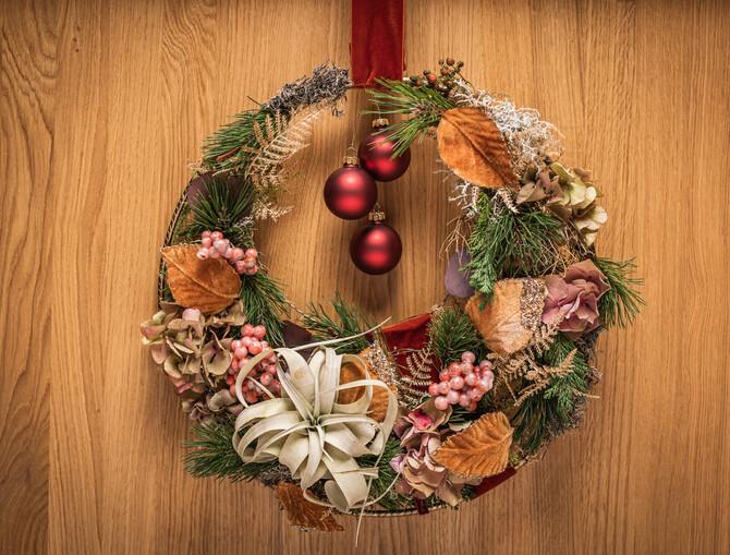 Ein moderner Kranz, gebunden auf einem runden Eisenring mit Tannenzweigen, Blättern, Moos, einer weißen Trockenblüte, rosa Beeren und drei hängenden roten Weihnachtskugeln in der Mitte