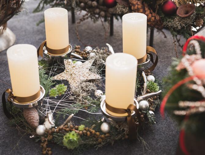 Ausgefallener Adventskranz auf einem runden Metallgestell mit 4 weißen Blockkerzen. Dekoriert ist das Gestell mit Koniferen Zweigen, Tannenzapfen und kleine silberne Weihnachtskugeln. In der Mitte ist mehrfach ein feiner Silberdraht gespannt und ein silberner Stern gelegt.