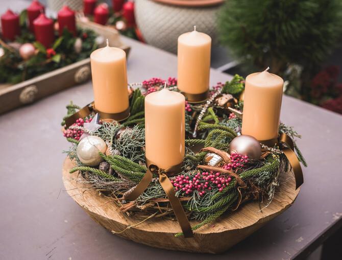Natürlicher runder Adventskranz in einer Teakschale mit beige Kerzen.