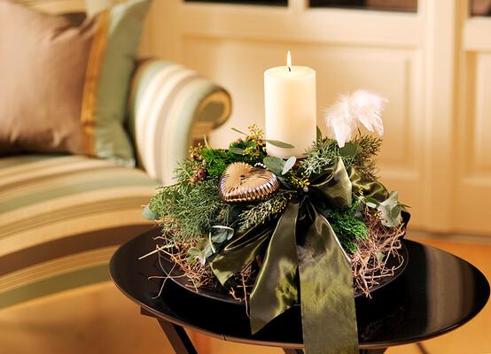 Eine liebevoll zusammengestellte Tischdekoration aus Tannenzweigen, einer weißen Kerze, einer weißen Feder, einem goldenen Herz und einer dunkelgrünen Masche auf einer Basis aus Zweigen