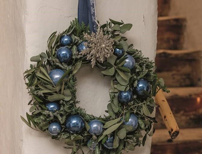 Ein festlicher Kranz aus Eukalyptus und Tannenzweigen gebunden, mit mehreren blauen Weihnachtskugeln und zwei goldenen Sternen, die mittig in der oberen Hälfte hängen