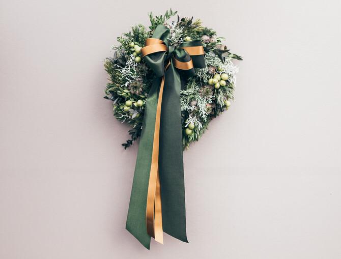 Voller Türkranz aus verschiedenen Zweigen, mit grünen Beeren und mit einer großen grün-goldenen Schleife mittig in der oberen Hälfte platziert