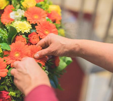 Detailaufnahme von einem Blumenkranz mit orangefarbenen Gerbera.