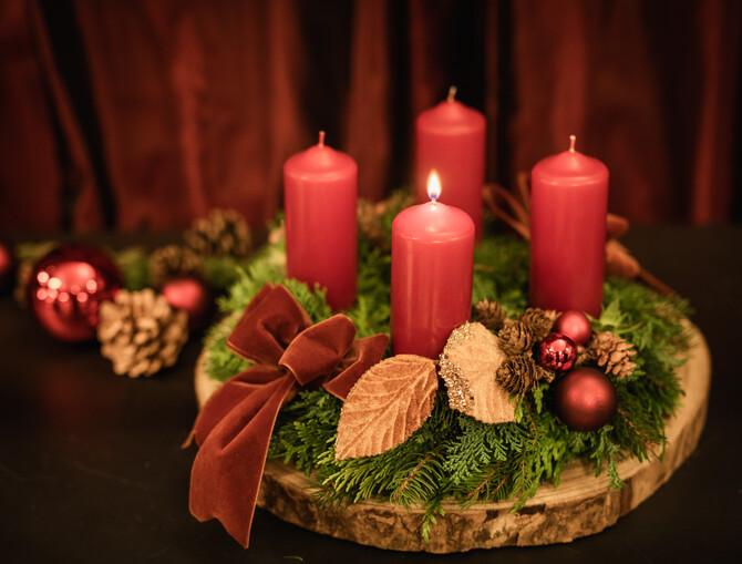 Ein traditioneller Adventkrant mit roten Kerzen, kleinen Tannenzweiten, einer kupferfarbenen Weihnachtskugel und einer Masche