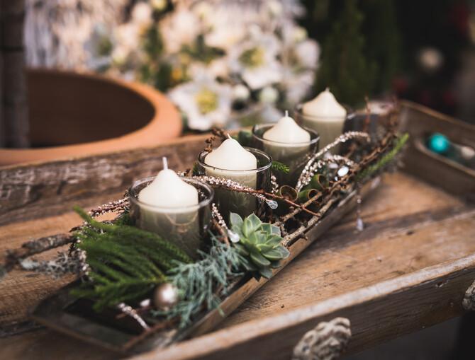 Adventskranz in einer länglichen Holzschale mit 4 weißen Kerzen in Gläsern. Dekoriert mit verschiedenen Naturzweigen.