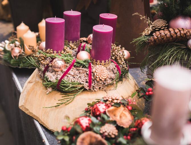 Bild mit mehreren Adventskränzen. Im Mittelpunkt steht ein runder Adventskranz, gebunden aus verschiedenen Naturmaterialien und lila Samtband. Die großen lila Blockkerzen stecken in dekorativen Kerzenhaltern.