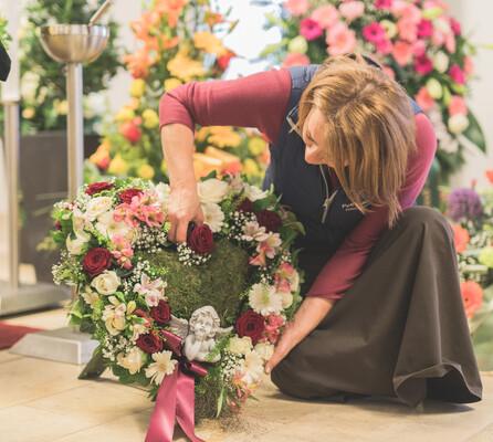 Am Boden kniende Floristin, die ein Grabgesteck in Herzform mit Blumen steckt.